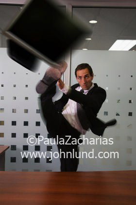 Business Man Kicking Laptop Computer Off Of Desk With A